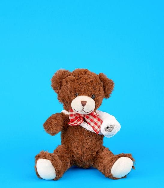 Urso de pelúcia marrom com rebobinado pata de bandagem branca sobre um fundo azul Foto Premium