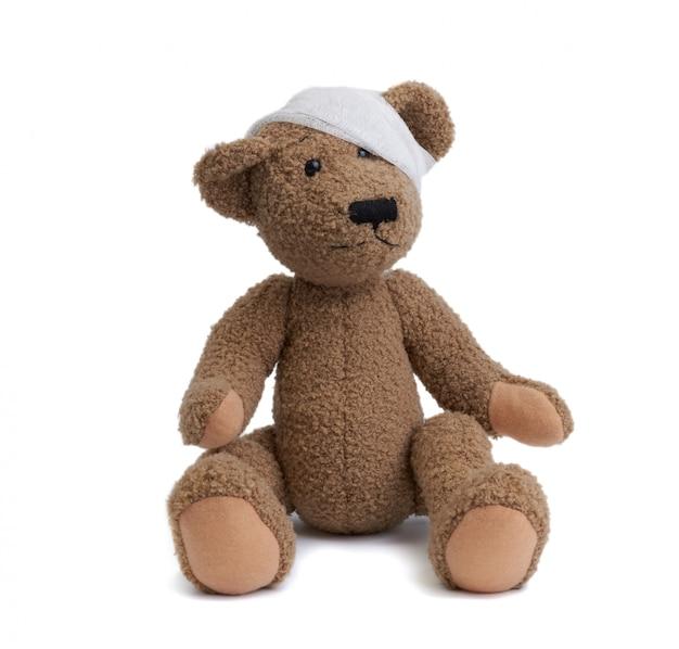 Urso de pelúcia marrom com uma cabeça enfaixada em uma bandagem médica branca sobre uma superfície branca Foto Premium