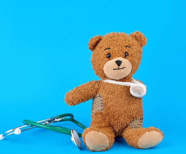 Urso de pelúcia marrom com uma pata enfaixada, sentado sobre um fundo azul Foto Premium