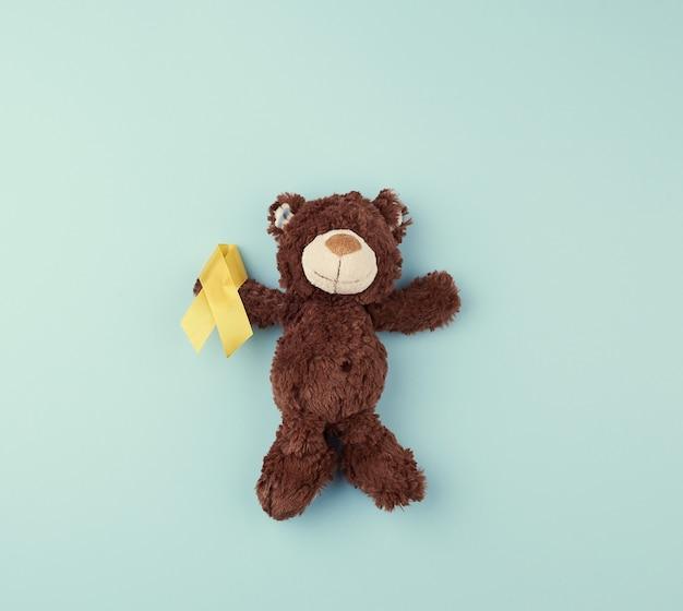 Urso de pelúcia marrom tem na pata uma fita amarela dobrada Foto Premium