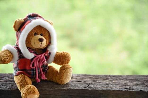 Urso de pelúcia na velha mesa de madeira verde natureza fundo Foto Premium
