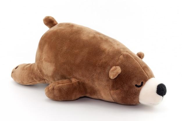 Urso marrom do brinquedo que dorme isolado no fundo branco Foto Premium