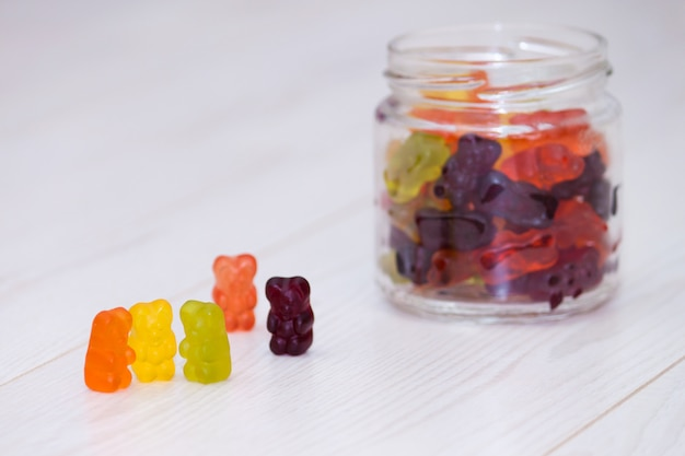 Ursos gomosos coloridos no fundo de madeira branco. conluio, amizade, conceito de tratado. Foto Premium