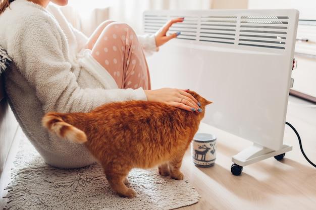 Usando aquecedor em casa no inverno. mulher aquecendo as mãos com gato. estação de aquecimento. Foto Premium