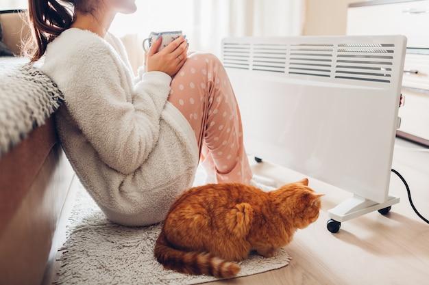 Usando aquecedor em casa no inverno. mulher aquecendo e bebendo chá com gato. estação de aquecimento. Foto Premium