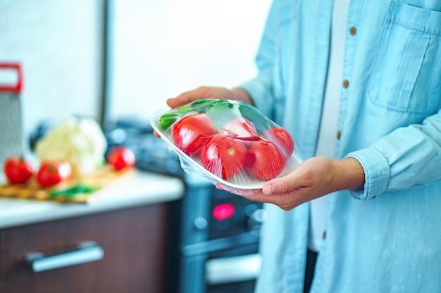 Usando filme alimentar para armazenamento de alimentos na geladeira Foto Premium