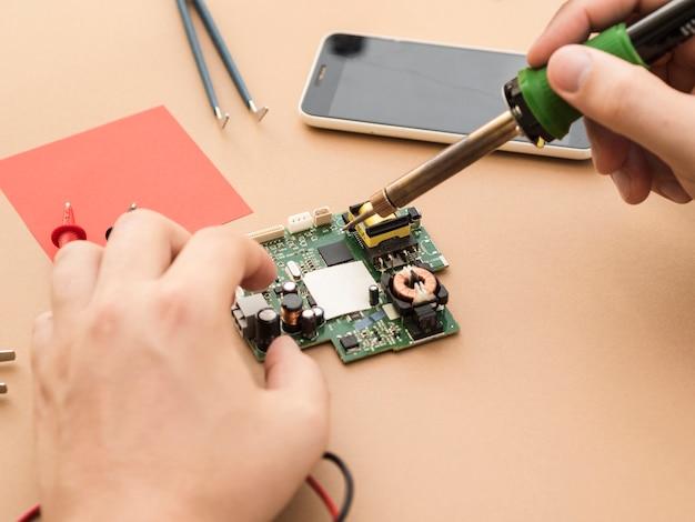 Usando o ferro de solda em um circuito Foto gratuita