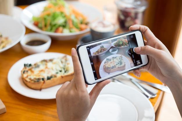 Use o celular para capturar sua refeição e compartilhe na rede social antes de comer Foto Premium