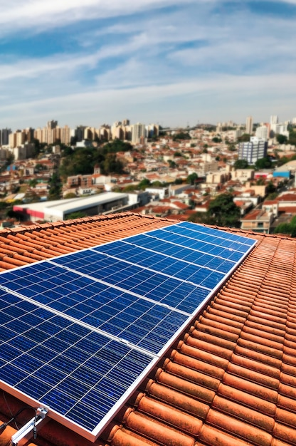 Usina fotovoltaica no telhado de um edifício residencial em dia ensolarado - conceito de energia solar de recursos sustentáveis Foto Premium