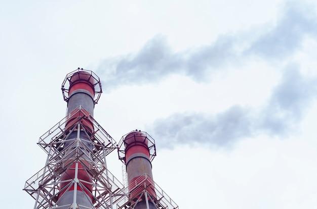 Usina termelétrica, a emissão de vapor e fumaça na atmosfera a partir de um tubo industrial, poluição ambiental. Foto Premium