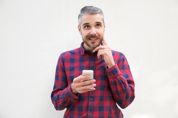 Usuário de celular pensativo positivo coçar a barba Foto gratuita