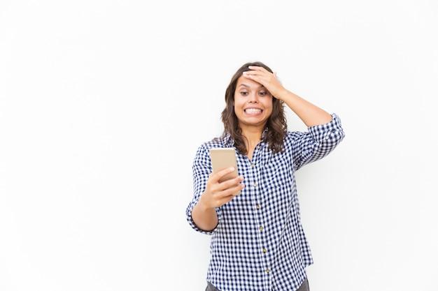 Usuário de smartphone envergonhado preocupado cometer erro Foto gratuita