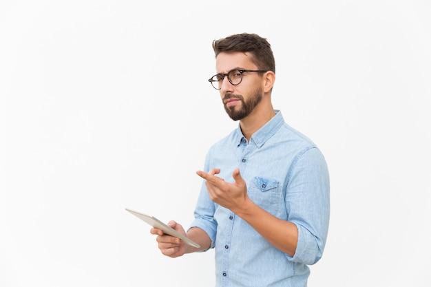 Usuário de tablet pensativo olhando e apontando o dedo para longe Foto gratuita