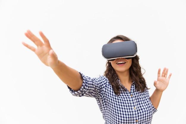 Usuário do sexo feminino positivo em óculos de realidade virtual, tocando o ar e sorrindo Foto gratuita