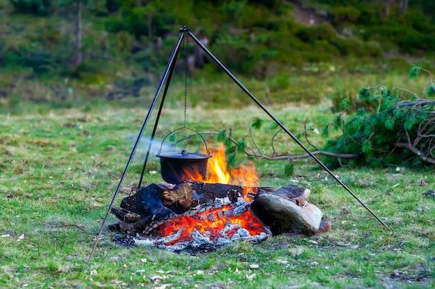 Utensílios de cozinha de acampamento - panela no fogo em um acampamento ao ar livre Foto Premium