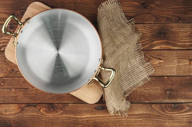 Utensílios de cozinha de cobre brilhante limpo na placa de madeira Foto Premium