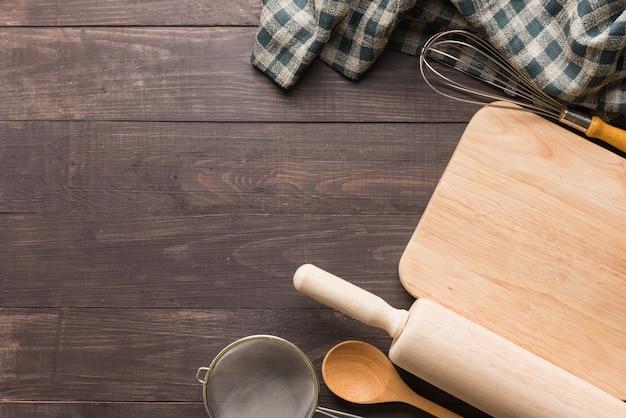 Utensílios de cozinha de madeira e guardanapo no fundo de madeira Foto Premium