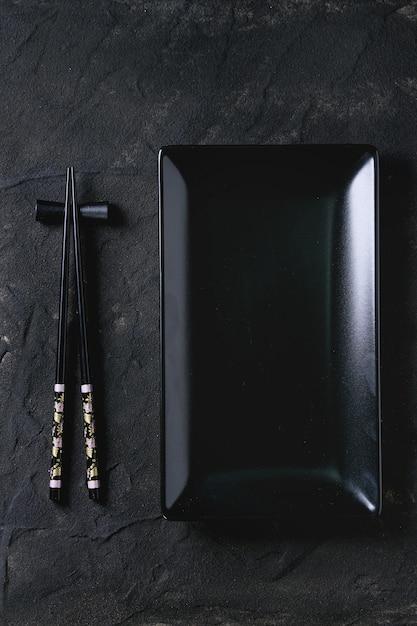 Utensílios de mesa asiáticos sobre preto Foto Premium