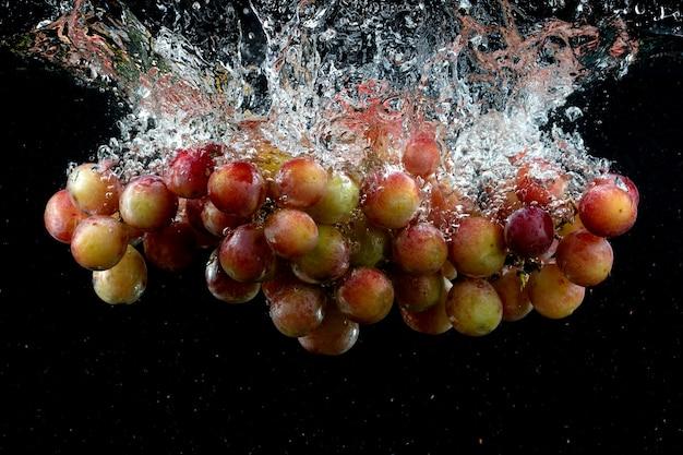 Uva espirrada na água no preto Foto gratuita
