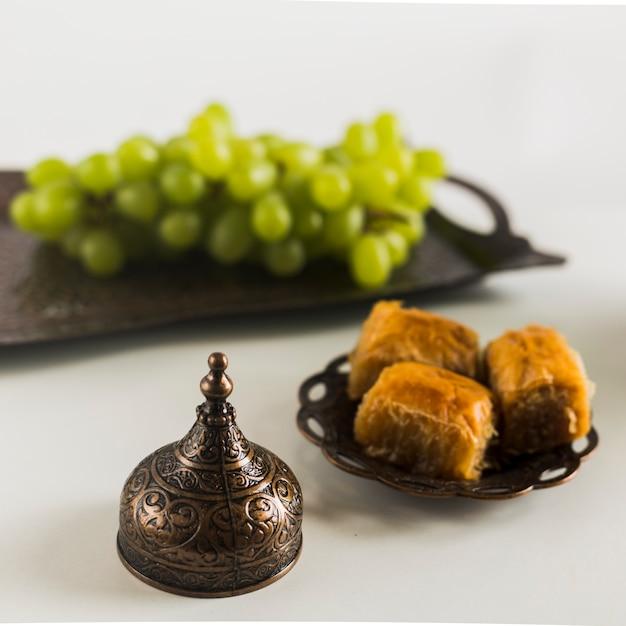 Uva na bandeja perto de baklava Foto gratuita