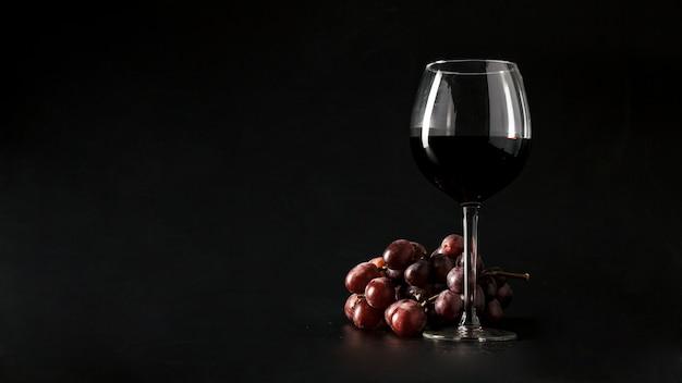 Uva perto de um copo de vinho Foto Premium