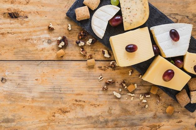 Uvas em blocos de queijo com frutas secas na mesa Foto gratuita