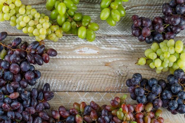 Uvas maduras em fundo de madeira, plana leiga. Foto gratuita