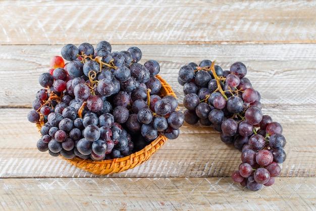 Uvas maduras em uma cesta de vime com fundo de madeira, vista de alto ângulo. Foto gratuita