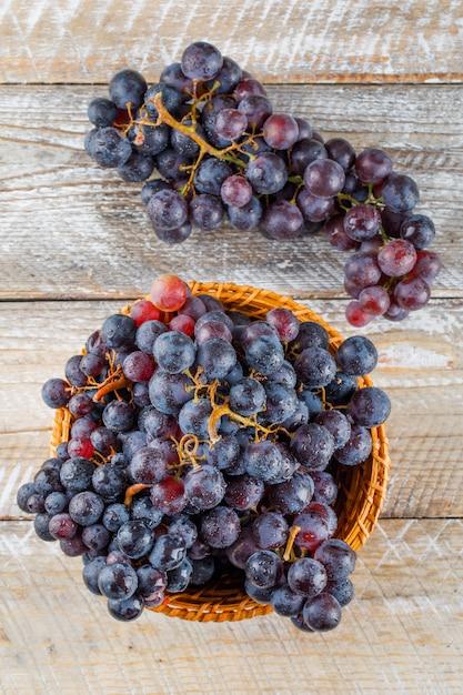 Uvas maduras em uma cesta de vime em um fundo de madeira. vista do topo. Foto gratuita