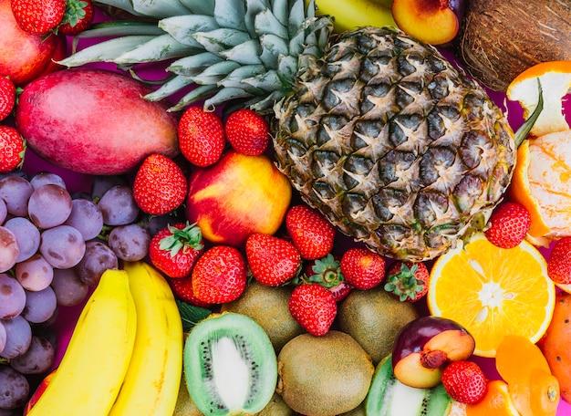 Uvas; morangos; abacaxi; kiwi; damasco; banana e abacaxi inteiro Foto gratuita
