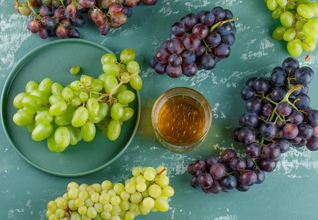 Uvas orgânicas com bebida em uma bandeja com fundo de gesso, vista superior. Foto gratuita