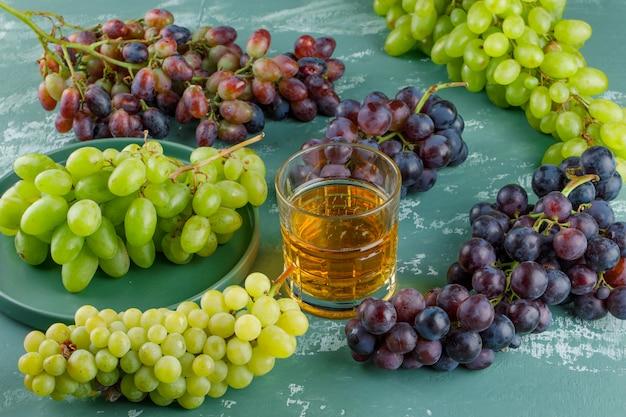 Uvas orgânicas em uma bandeja com vista de alto ângulo da bebida em um fundo de gesso Foto gratuita
