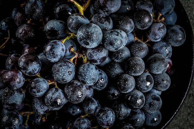 Uvas pretas do agricultor orgânico natural cru cachos na placa preta fundo escuro pedra vista superior perto Foto Premium