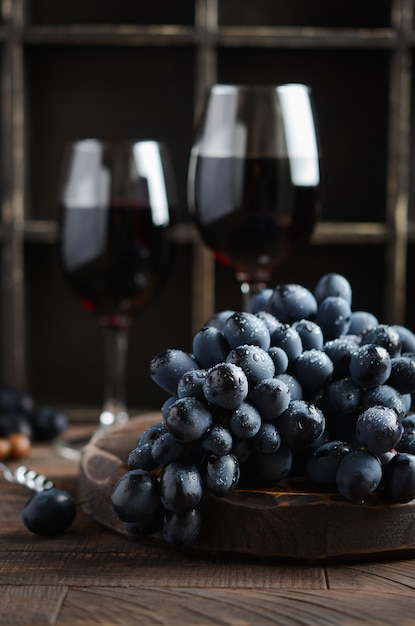 Uvas pretas frescas e vinho tinto na mesa de madeira Foto Premium