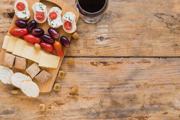 Uvas, tomates, fatias de queijo, pão e bolos com copo de vinho na mesa de madeira Foto gratuita