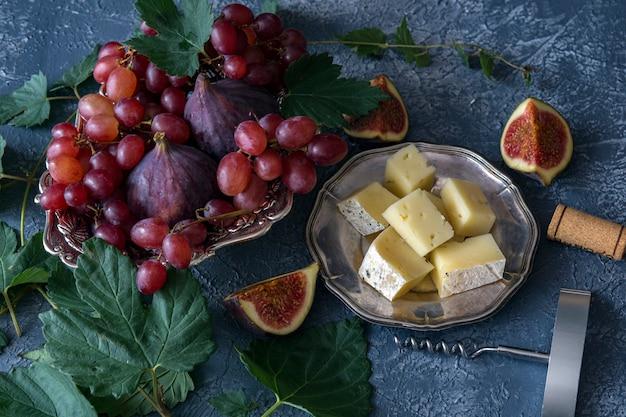 Uvas vermelhas, figos, queijo, saca-rolhas e cortiça de vinho e em torno da videira Foto Premium