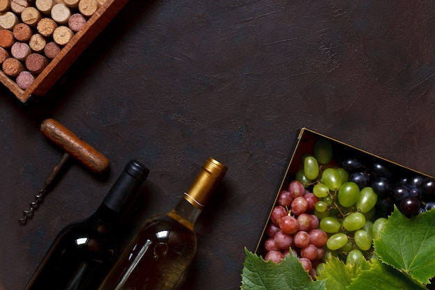 Uvas vermelhas, verdes e azuis com folhas em caixa de metal Foto Premium