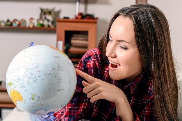 Vá em uma aventura, mulher sonhando em viajar ao redor do mundo, olhando para o globo na sala da casa, feliz linda morena se preparando para a viagem, Foto Premium