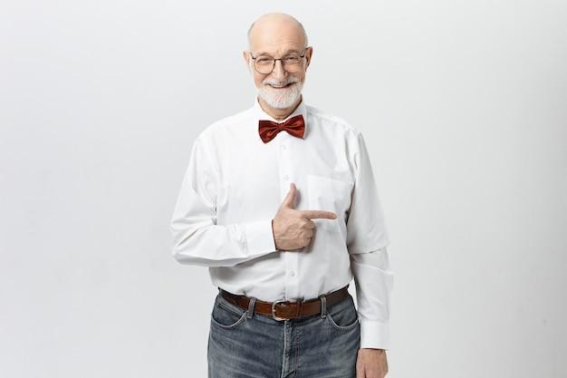 Vá por este caminho. alegre simpático pensionista masculino em roupas elegantes, apontando o dedo indicador, mostrando como chegar ao museu. homem sênior atraente indicando parede com copyspace para seu texto Foto gratuita