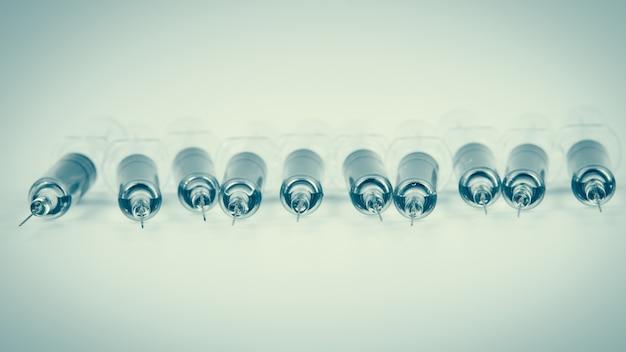 Vacina contra a gripe, hpv, vacina contra o sarampo com seringa e agulha Foto Premium