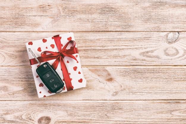 Valentim ou o outro presente feito a mão do feriado no papel com corações vermelhos, chaves do carro e caixa de presentes no envoltório do feriado. presente da caixa na opinião de tampo da mesa de madeira alaranjada com espaço da cópia, espaço vazio para o projeto Foto Premium