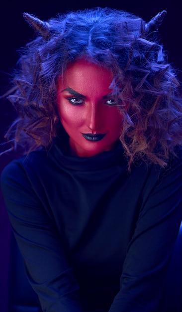 Vampiro de menina belo retrato com pele vermelha e chifres na cabeça, olhos brilhantes com lábios pretos Foto Premium