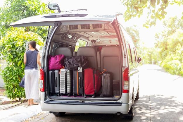Van com bagagem em um arenoso com a mulher no conceito do curso do backgroung do borrão. Foto Premium