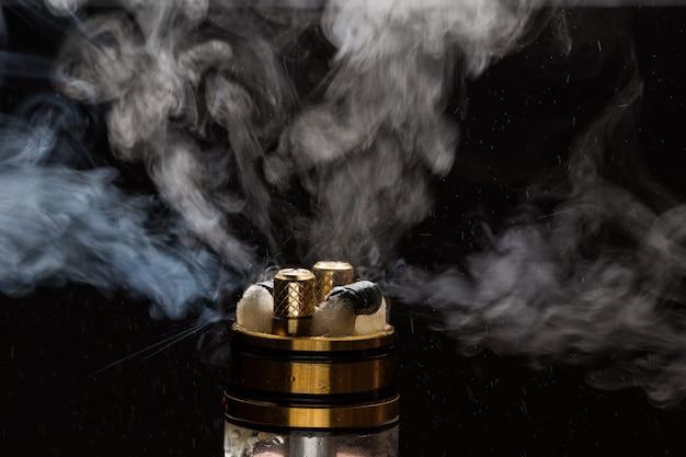 Vape close-up com fumo em um fundo preto Foto Premium