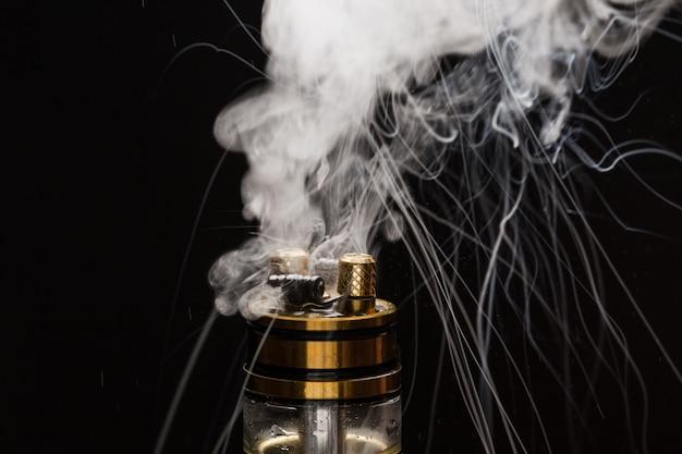 Vape com fumaça em um preto Foto Premium
