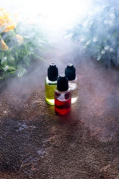 Vape do conceito. elíquido com nuvens de fumaça frescas garrafas de líquido Foto Premium