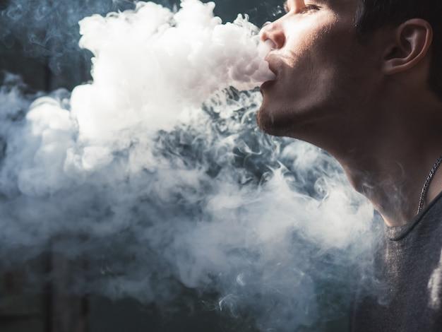 Vaper masculino em uma nuvem escura do close up do fundo do vapor Foto Premium