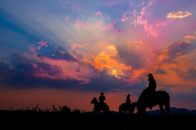 Vaqueiro a cavalo com vistas das montanhas e do céu do por do sol. Foto Premium