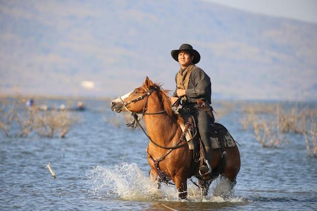 Vaqueiro, montando um cavalo no rio Foto Premium