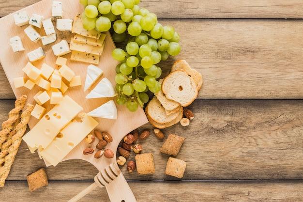 Varas de pão, queijo bloqueia, uvas, pão e biscoitos na mesa de madeira Foto gratuita